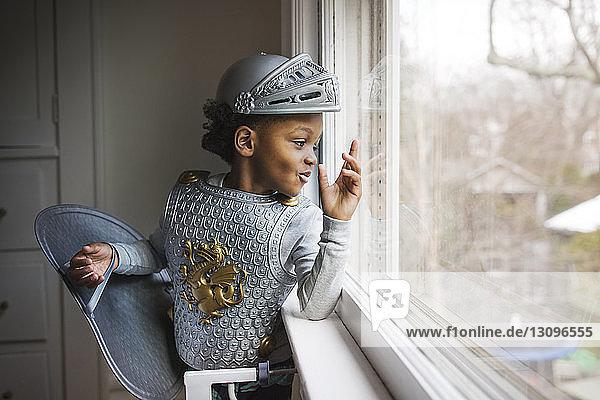 Neugieriger Junge im Panzerkostüm  der zu Hause aus dem Fenster schaut