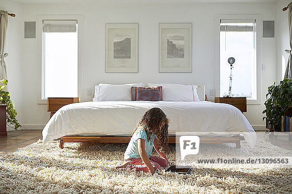 Side view of girl using tablet computer while kneeling on rug in bedroom