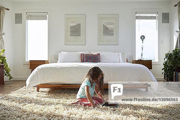 Seitenansicht eines Mädchens  das einen Tablet-Computer benutzt  während sie im Schlafzimmer auf dem Teppich kniet