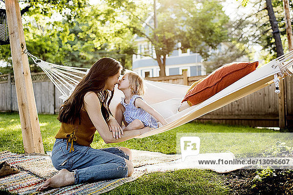 Daughter kissing mother while sitting in hammock at yard