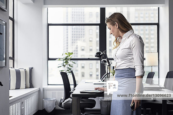 Businesswoman using tablet computer on desk while standing in office
