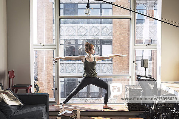 Full length of woman practicing warrior pose by window at home