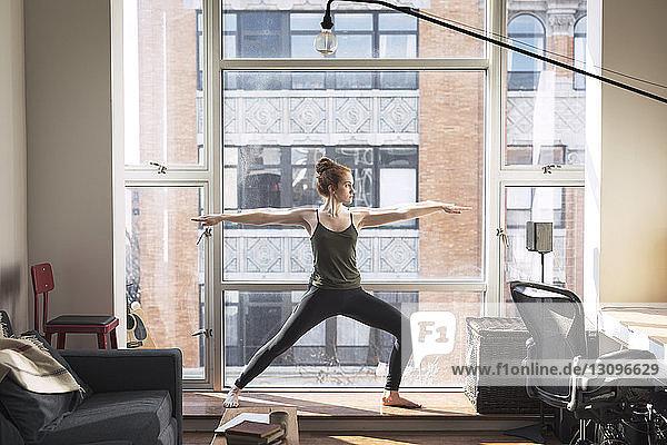 Eine Frau in voller Länge übt zu Hause am Fenster eine Kriegerpose aus