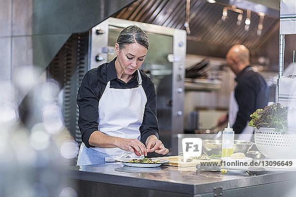 Köchin beim Garnieren von Speisen  während eine Mitarbeiterin im Hintergrund in der Restaurantküche arbeitet