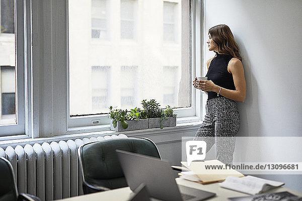 Nachdenkliche Geschäftsfrau mit Kaffeetasse,  die durch das Fenster schaut,  während sie im Büro an der Wand steht