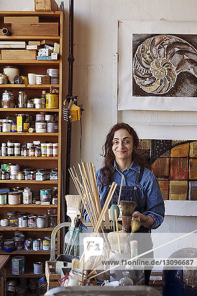Portrait of smiling artist standing by shelf in workshop