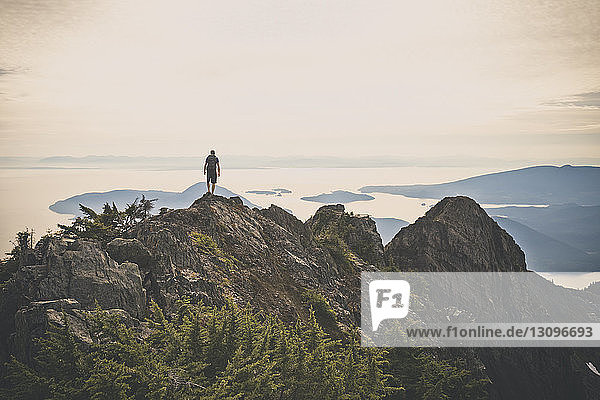 Rear view of hiker standing on mountain against sky