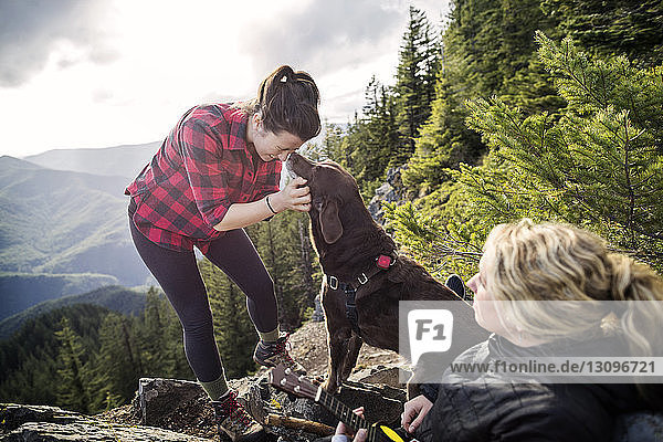 Women enjoying with dog on mountain cliff against sky