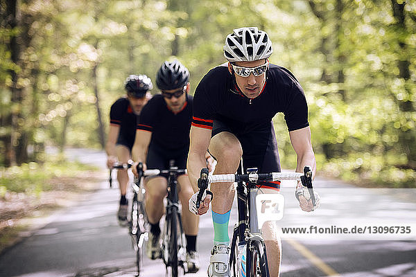 Confident male cyclist riding bicycle with friends on country road