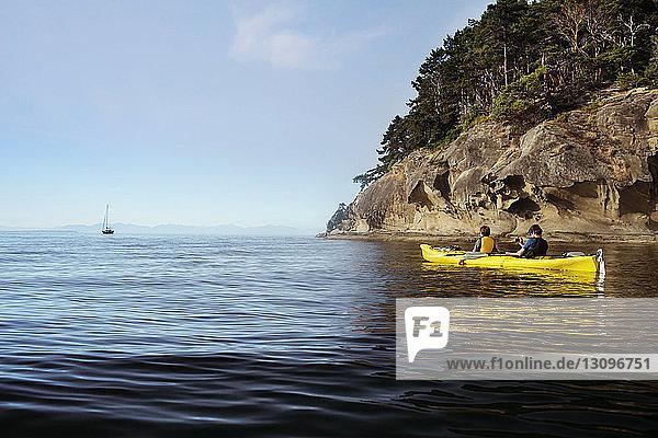 Rear view of men kayaking at Strait of Georgia