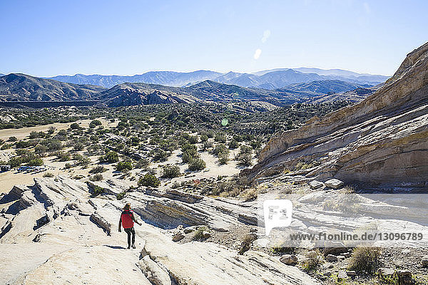 High angle view of hiker walking on landscape against blue sky on sunny day