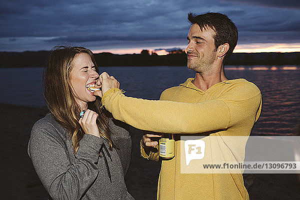 Man feeding smore to female friends against river during sunset