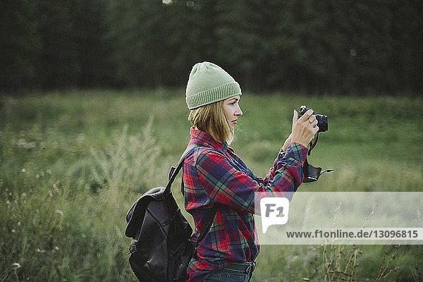 Frau mit Rucksack beim Fotografieren im Stehen auf Grasfeld