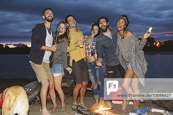 Happy friends at campfire by river against cloudy sky