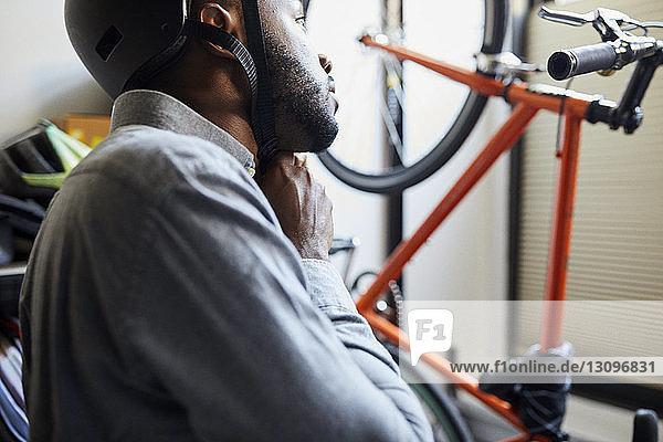 Geschäftsmann mit Fahrradhelm im Kreativbüro