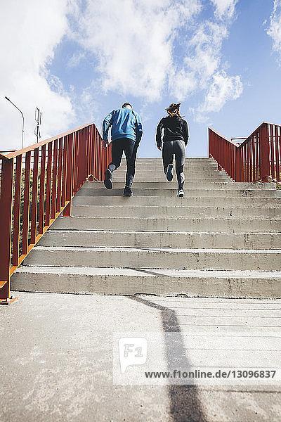Tiefwinkelansicht eines Paares  das sich auf Stufen gegen den Himmel nach oben bewegt