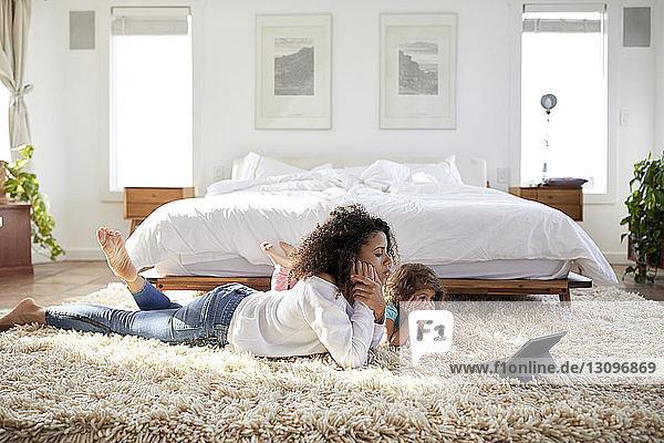 Mutter und Tochter schauen auf Tablet-Computer  während sie im Schlafzimmer auf dem Teppich liegen