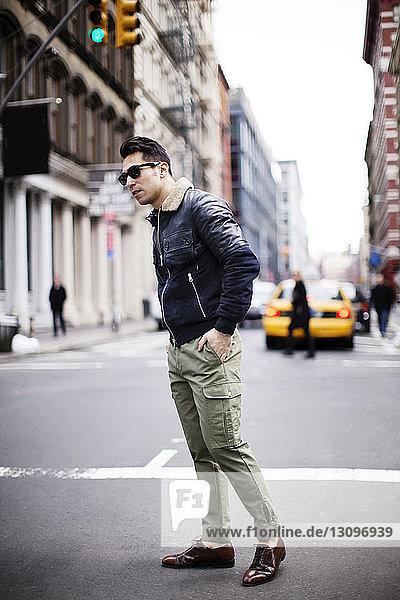Man standing on street against buildings