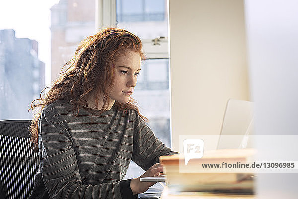 Confident woman using laptop computer while sitting by window at home