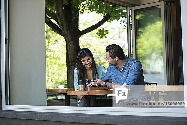 Glückliches Paar  das im Café sitzend durchs Fenster auf sein Handy schaut