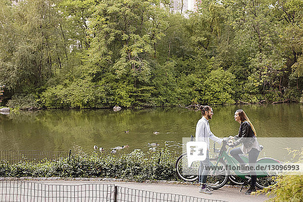 High angle view of happy couple talking while standing with bicycles by lake