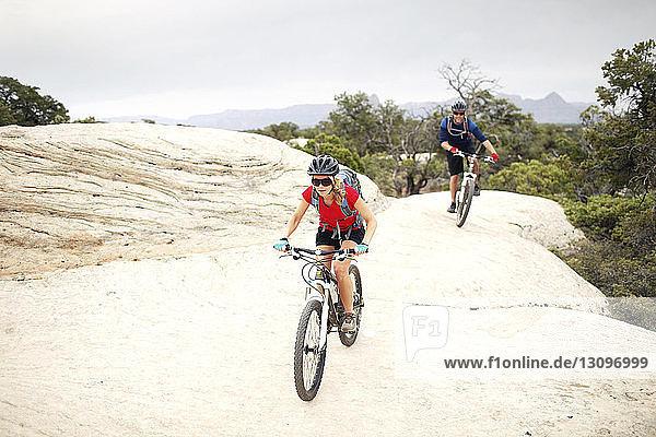 Fahrrad fahrende Paare auf Felsen vor klarem Himmel