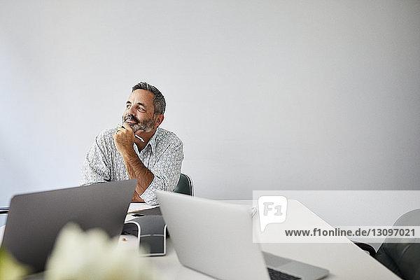 Nachdenklicher Geschäftsmann mit der Hand am Kinn  der am Konferenztisch im Sitzungssaal an der Wand sitzt