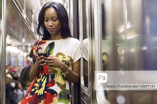 Woman using phone while traveling in train