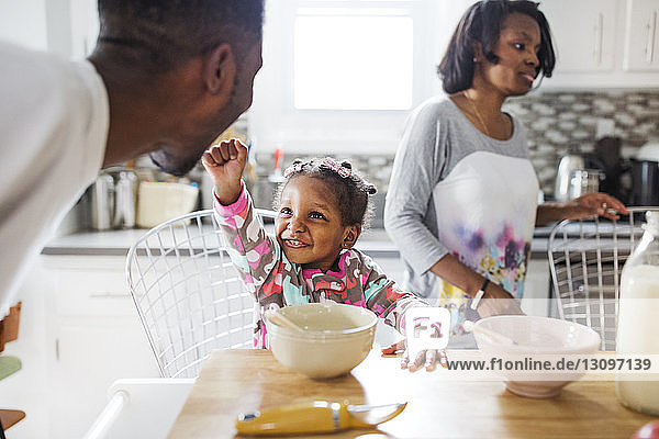 Cheerful girl playing with father in kitchen