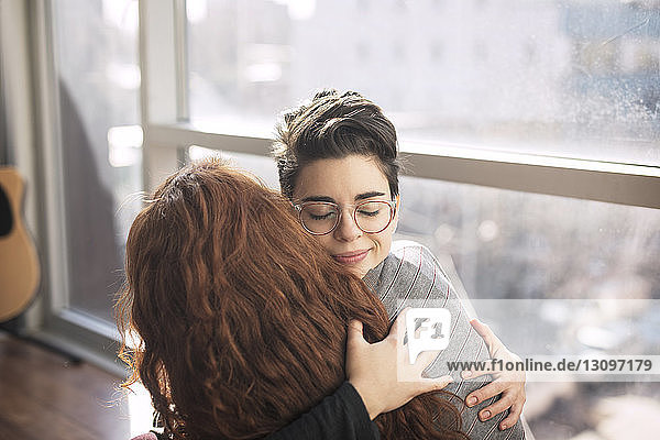 High angle view of lesbian couple embracing by window at home