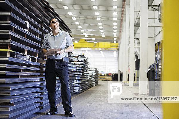 Nachdenklicher Vorgesetzter schreibt in voller Länge auf dem Klemmbrett  während er bei den Blechen in der Fabrik der Stahlindustrie steht