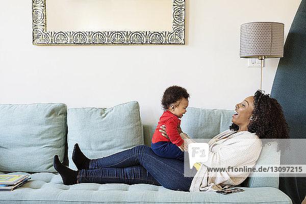 Glückliche Frau spielt mit ihrem Sohn  während sie zu Hause auf dem Sofa sitzt