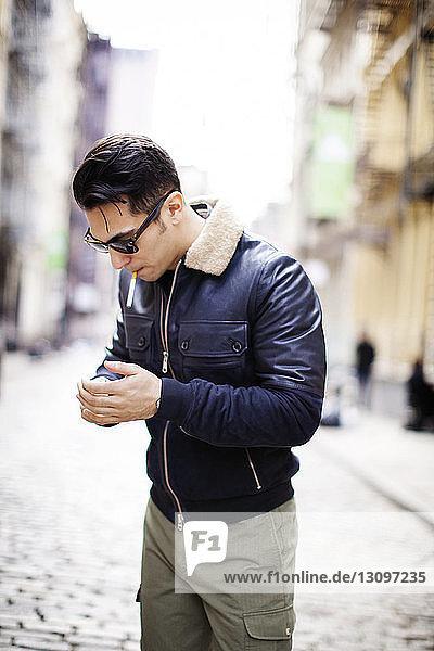 Mann steht auf der Straße und zündet Zigarette an