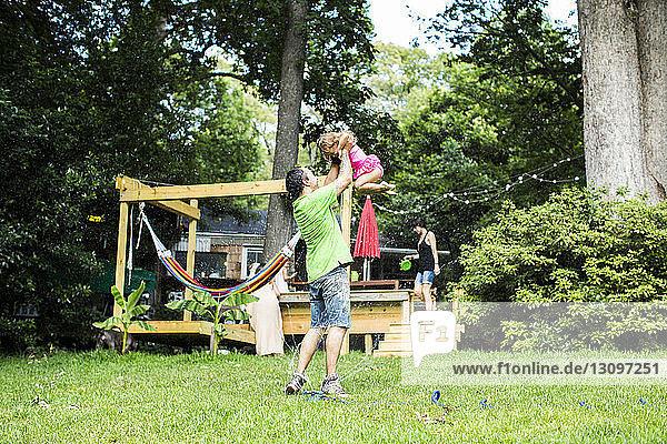 Verspielter Vater hebt Tochter im Hinterhof hoch