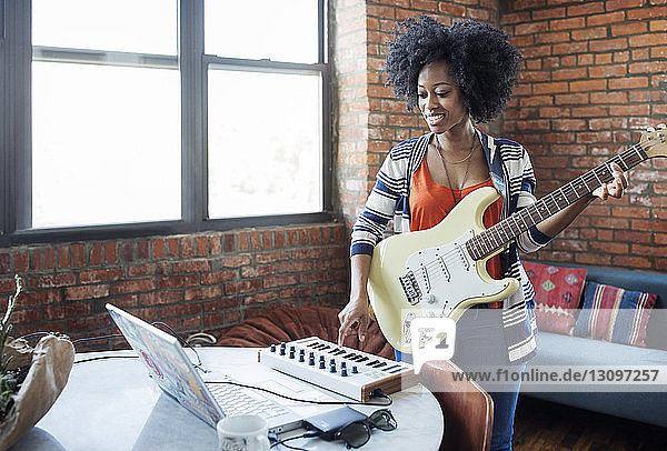 Woman playing piano while holding guitar at home