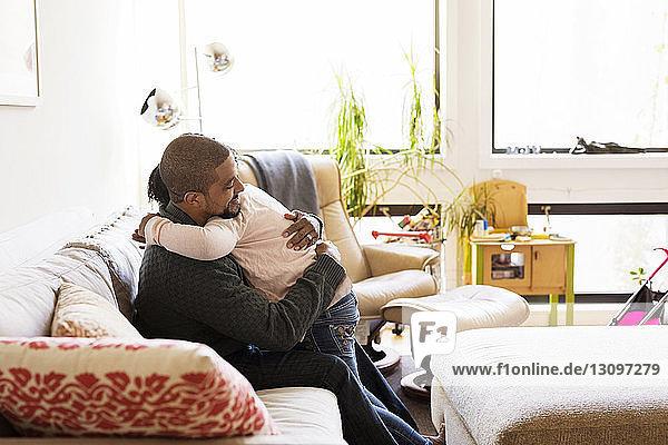 Seitenansicht eines Mannes  der seine Tochter umarmt  während er auf dem Sofa sitzt