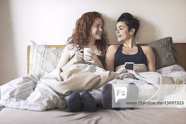 Happy lesbian couple looking at each other while sitting on bed