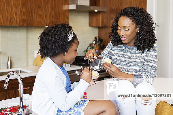 Mother and daughter eating cupcakes while sitting on kitchen island