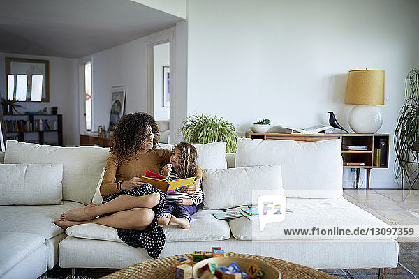 Mother reading picture book for daughter while sitting on sofa at living room