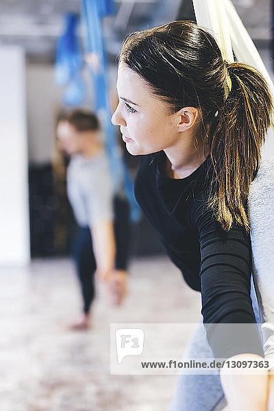 Freunde praktizieren Luftyoga im Fitnessstudio