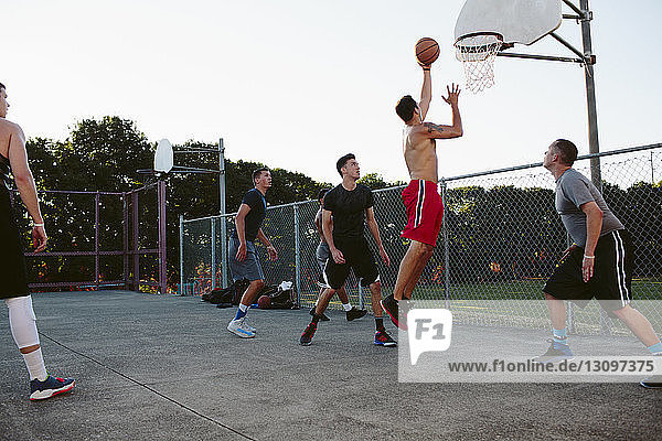 Friends looking at player making basket while playing in court