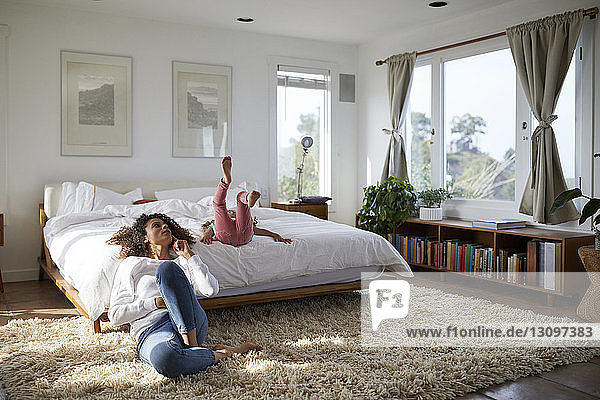 Mother and daughter relaxing in bedroom at home