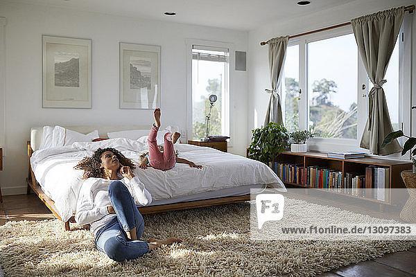 Mutter und Tochter entspannen sich zu Hause im Schlafzimmer