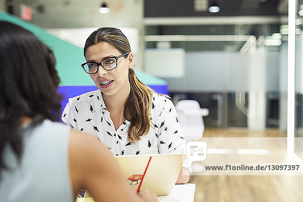 Confident businesswoman discussing with colleague at table in office cafeteria