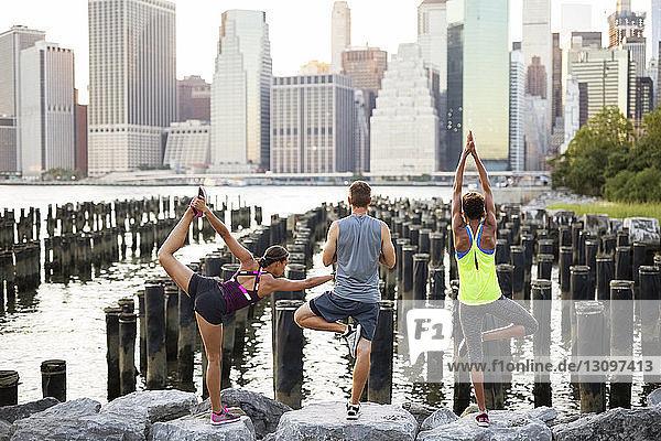 Rückansicht von Athleten  die auf einem Felsen am Fluss trainieren