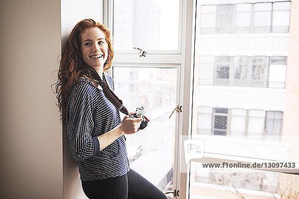 Lächelnde Frau mit Kamera  die weg schaut  während sie sich zu Hause am Fenster an die Wand lehnt