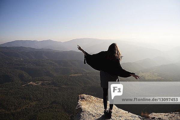 Rückansicht einer Frau  die gestikulierend auf einer Klippe vor Bergen steht