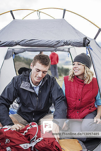 Couple sitting in tent at campsite