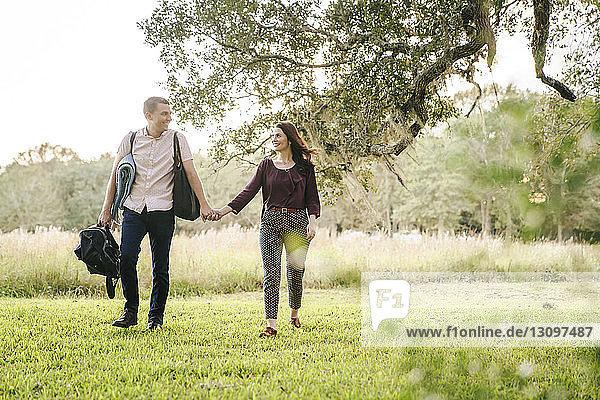 Lächelndes Paar hält sich beim Spaziergang auf dem Grasfeld im Park an den Händen