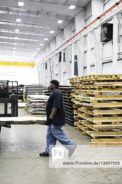 Seitenansicht eines Arbeiters  der in einer Fabrik der Stahlindustrie geht